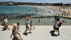 People commute on a walkway as others cool off in the water during heatwave conditions at Bondi Beach in Sydney
