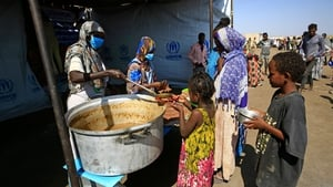 Ethiopian refugees who have fled the Tigray conflict receive food at a transit centre in Sudan's border town of Hamdayit on 27 November