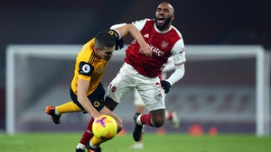 Conor Coady of Wolves and striker Alexandre Lacazette clash at the Emirates.
