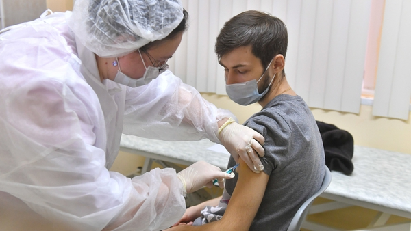A Russian medic administering a coronavirus vaccine to a man in Moscow today