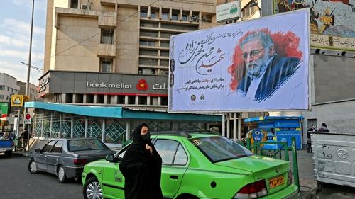 A woman walks past a billboard showing Mohsen Fakhrizadeh in Tehran