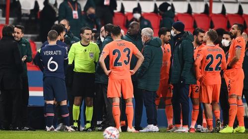 Romanian referee Ovidiu Hategan (in yellow) talks to Istanbul Basaksehir's staff members before they walk off