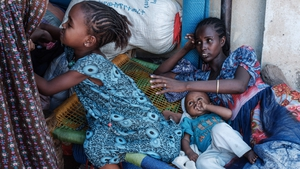 An Ethiopian family rests in a makeshift shelter in Sudan after fleeing conflict in Tigray