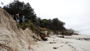 People watch the long stretch of beach at Byron Bay that disappeared due to wild winds, high seas and rain