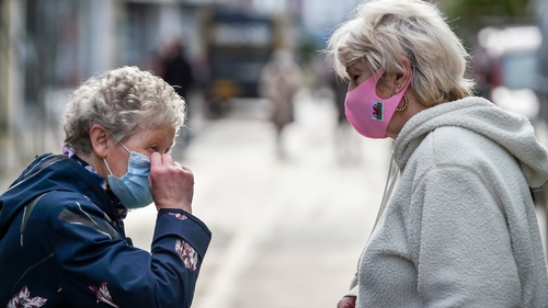 People chat on the High Street in Merthyr Tydfil, the area with the highest seven-day coronavirus case rate in Wales