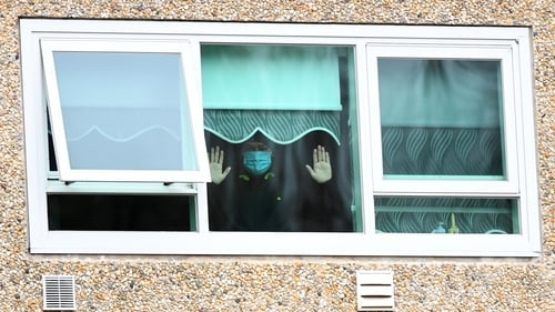 A resident of one of the towers in Melbourne looking out his window during lockdown last July