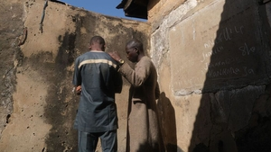 A boy who escaped from the gunmen stands with his father in their home in Kankara town