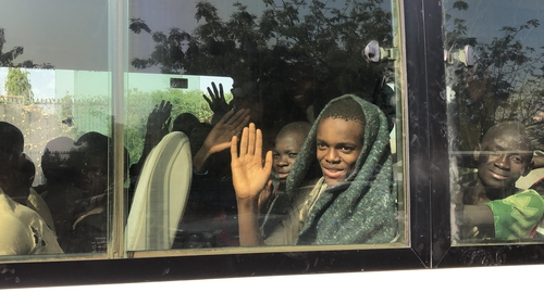 A boy waves from a bus full of children following their release