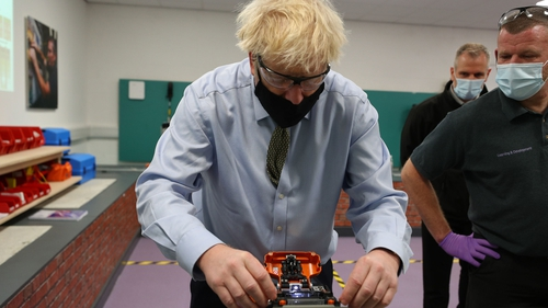 Boris Johnson tries his hand at cable splicing during a visit to a training centre in Greater Manchester