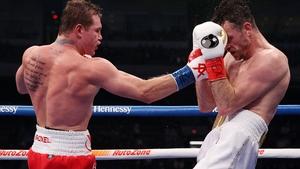 Canelo Alvarez (L) lands a punch on Callum Smith