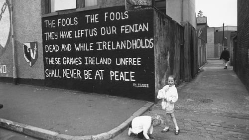 Two girls pictured near a mural on the Falls Road in Belfast c1990