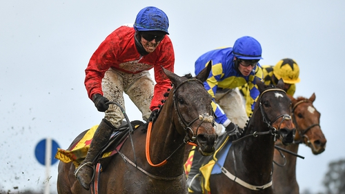 Jockey Darragh O'Keeffe, left, celebrates as he passes the finishing post after riding A Plus Tard to victory in the Savills Steeplechase
