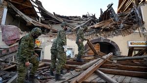 Croatian soldiers walk on wreckage next to damaged buildings in Petrinja