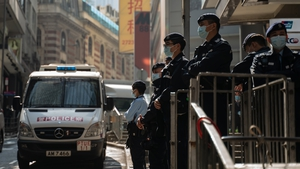 Police officers stand guard near the office of human rights lawyer John Clancey