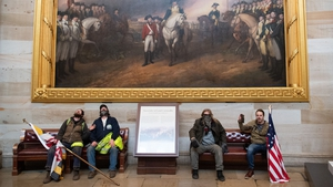 Trump supporters take a seat beneath a painting showing the final surrender of British troops under Lord Cornwallis after the Battle of Yorktown in 1781