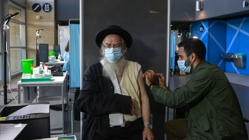 A healthcare worker administers the vaccine to an ultra-Orthodox Jewish man at Clalit Health Services in Jerusalem
