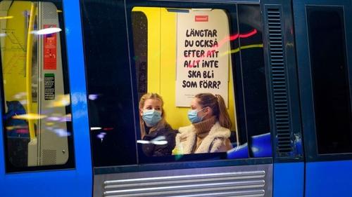 Passengers on an underground train wear masks in Stockholm