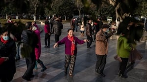 People dance in a busy park next to the Yangtze river