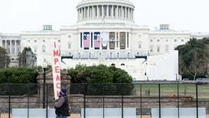 Workers hang flags on the US Capitol for the inauguration as a man carrying an impeach sign protests nearby