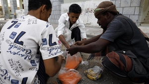 Yemenis share grain of food rations provided by an aid group, amid a dire humanitarian crisis, in the western port city of Hodeidah