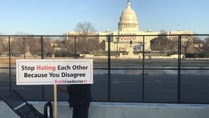 A man holds a sign urging unity near the US Capitol