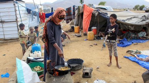 Children play near tents as a woman cooks outdoors at a makeshift camp for the displaced