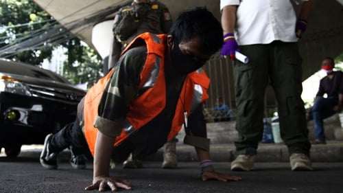 A resident does push-ups in May last year as a sanction for breaking large-scale social restriction regulations in Indonesia