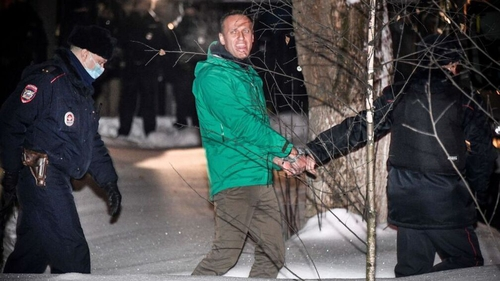 Alexei Navalny is escorted out of a police station on 18 January
