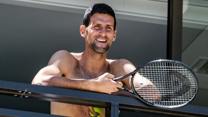Djokovic smiles at fans from a hotel balcony in Adelaide