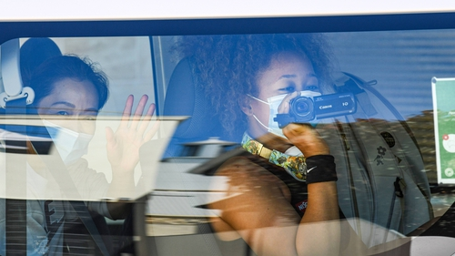 Women's world number three tennis player Naomi Osaka uses a video camera as she returns to her hotel after a practice session in Australia
