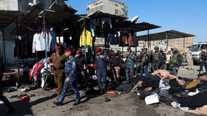 Officials inspect the explosion site at al-Tayaran Square