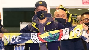 Mesut Ozil holds up a Fenerbahce scarf in Istanbul