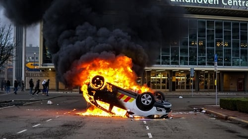 A car is overturned and set ablaze during a protest near Eindhoven Central Station yesterday
