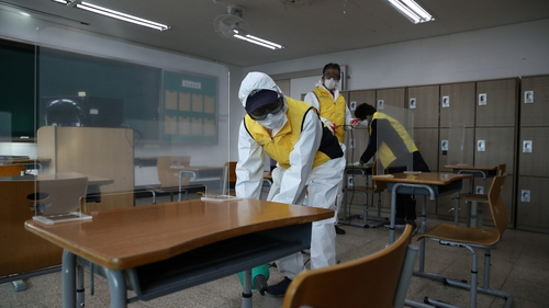 Workers sanitise a classroom in Seoul