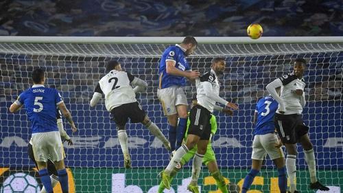 Brighton defender Adam Webster (C) wins a header