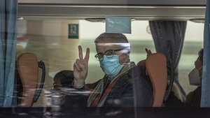 A member of the WHO team gestures from a bus as he leaves the Jade Boutique hotel