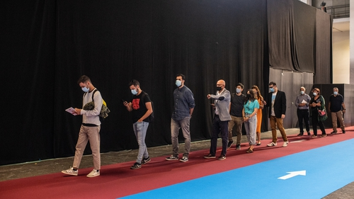 Participants observe social distancing guidelines as they stand in a queue during a job and employment fair in Barcelona