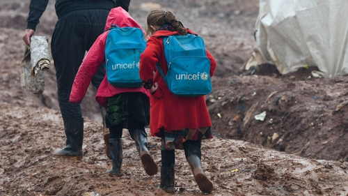 Children are led to school in the Atme camp close to the border with Turkey in Syria's northwestern Idlib province