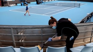 Seating areas around the court being cleaned during a warm-up session at Melbourne Park today