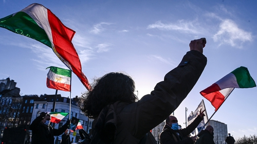 People gesture and wave former flags of Iran as they protest outside the Antwerp criminal court