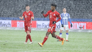 Bayern Munich goalscorer Kingsley Coman celebrates as the snow falls at the Olympiastadion in Berlin