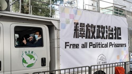 Activist chants protest slogans inside a van outside the Lai Chi Kok Reception Centre