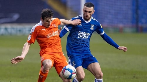 Troy Parrott battles for possession with Blackpool's Matty Virtue