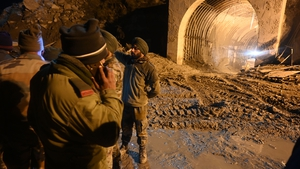 Rescue teams outside the entrance of a tunnel blocked with mud and debris in Tapovan, India following a flash flood