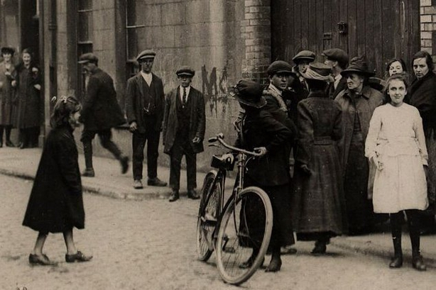 Woman standing with a bicycle near the spot where Kevin Barry was arrested in September 1920 Photo: National Library of Ireland, HOGW 127