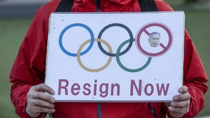 A man holds placard outside Japan Olympic Museum calling for the resignation of Yoshiro Mori.