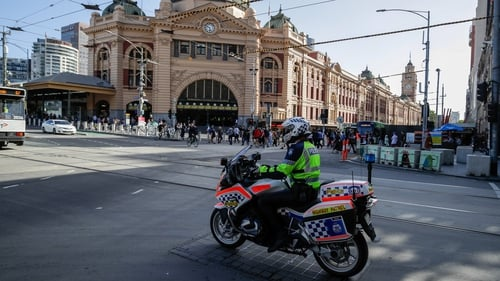 A policeman patrols on a motorcycle in Melbourne after authorities ordered a five-day state-wide lockdown