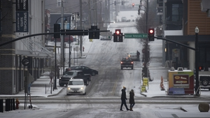 People cross a road in Nashville, Tennessee, after an overnight mix of sleet and freezing temperatures coated the city in ice