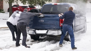 People help push a pickup stuck in the snow at Round Rock, Texas