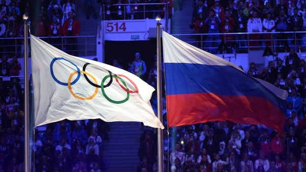 The Olympic flag (L) and the Russian flag flutter during the Closing Ceremony of the Sochi Winter Olympics
